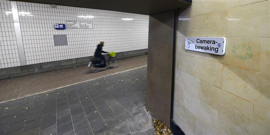 Fietser rijdt door een tunnel met camerabewaking.