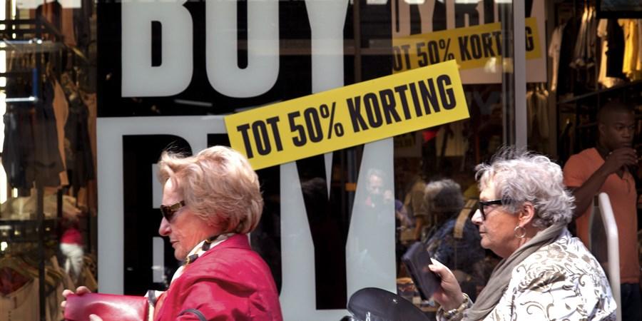 vrouwen lopen langs etalage van winkel die uitverkoopt