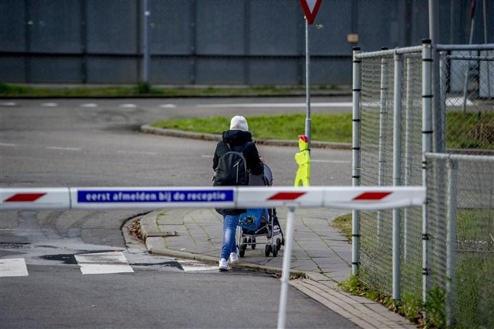 Jonge vrouw met kinderwagen passeerd slagboom van een asielzoekerscentrum