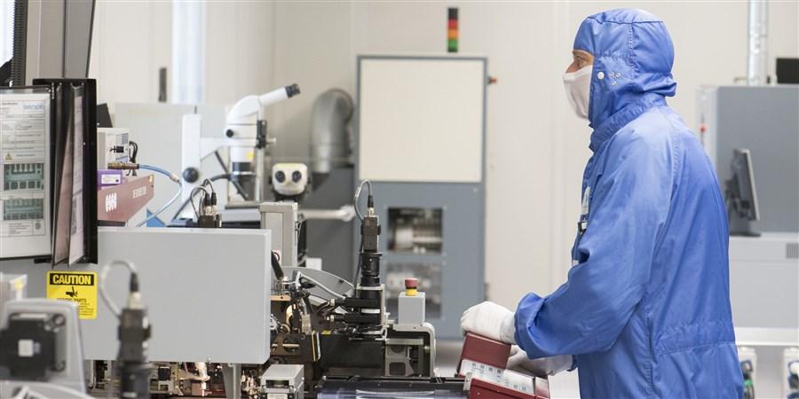 Een medewerkers van een chipfabriek waar microprosessors worden geassanbleerd
