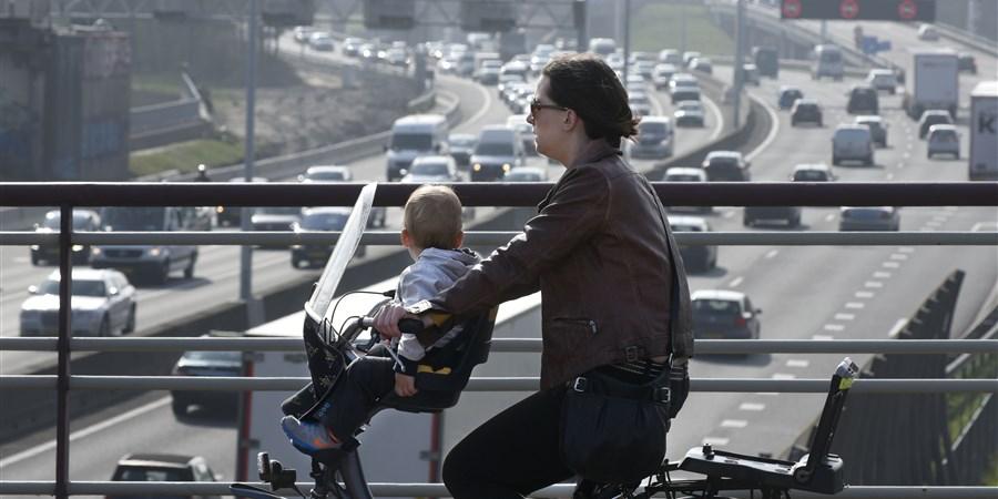 Nederland, Rotterdam, fietser moeder met kind op viaduct over de A20, een van de drukste snelwegen van Nederland