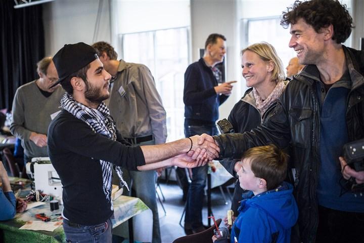 Vluchtelingen uit Syrie werken mee in het Repair Cafe in de stad Groningen. Een syrische jongen schut een nederlands gezin de hand.