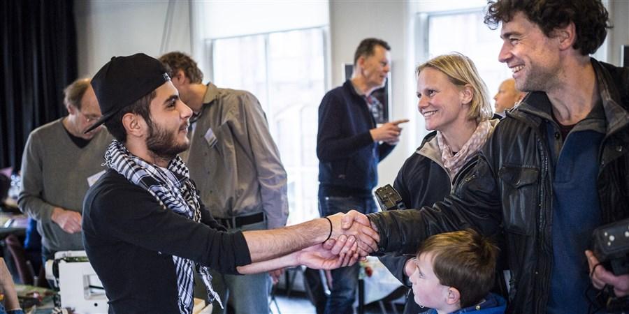 Vluchtelingen uit Syrië werken mee in het Repair Café in de stad Groningen. Een Syrische jongen schudt een Nederlands gezin de hand.
