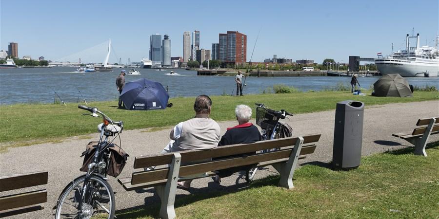 Ouder echtpaar zit aan de Maas in Rotterdam.