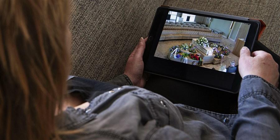 Een vrouw kijkt via een iPad naar een uitvaart. Door de corona-maatregelen kunnen maar een klein aantal mensen aanwezig zijn. De begrafenisonderneming zorgt voor een link waar je als genodigde kan inloggen voor een live-verbinding.