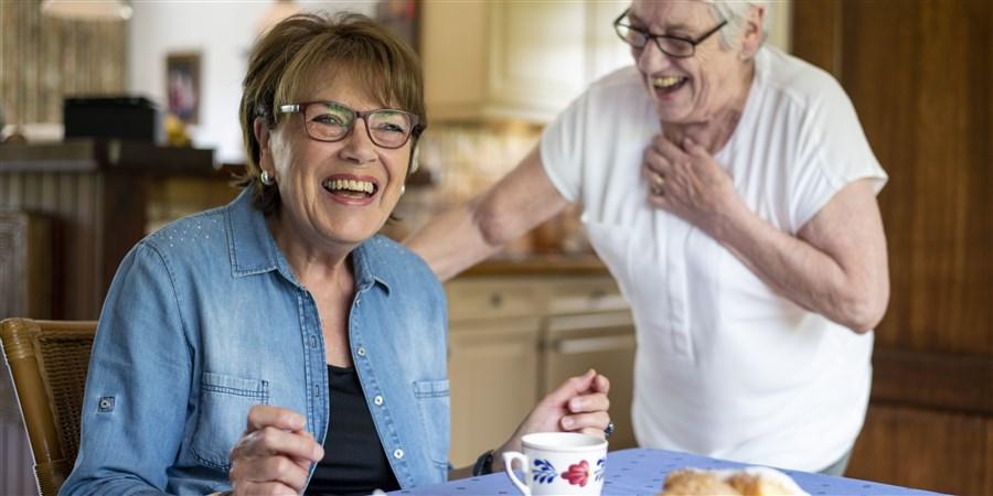 Twee oudere zussen genieten van een kopje koffie