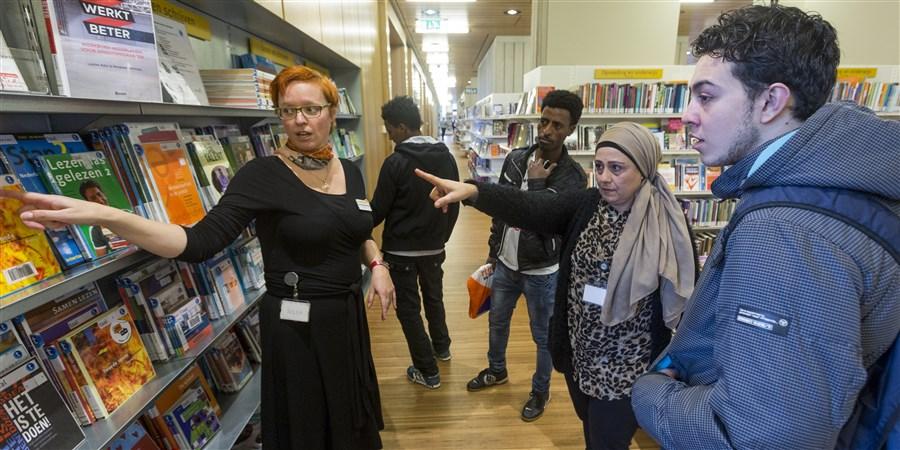 Een groep jongeren krijgt een rondleiding in een bibliotheek