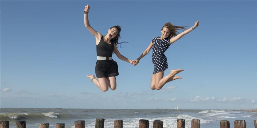 Twee vriendinnen springen van de  golfbekers af in het water met vloed.
