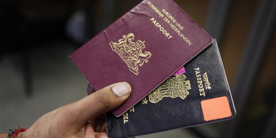 Hand met Nederlands en Indiaas paspoort