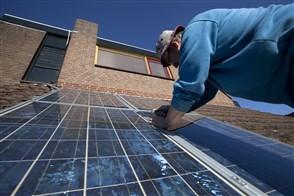 Man monteert zonnepanelen op het dak van een woning