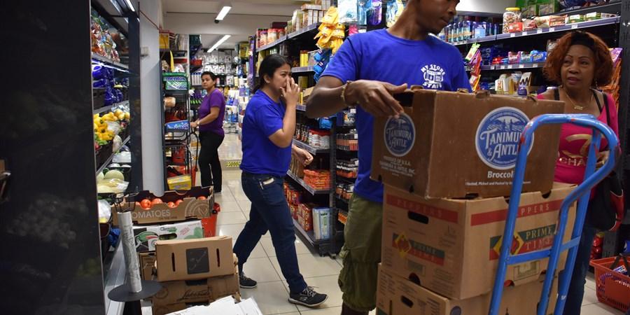 Een man tilt dozen van een steekwagen in een supermarkt