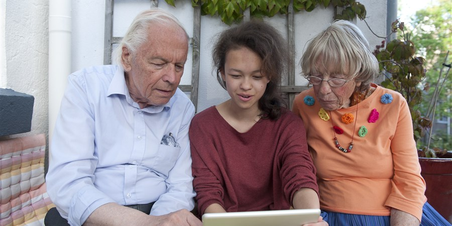 Opa en oma met kleindochter kijkend naar de ipad.