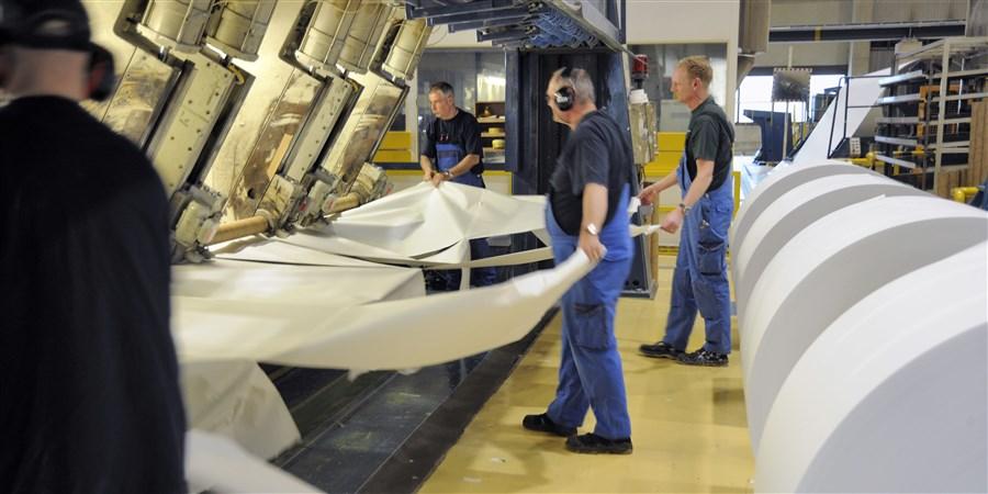 Werknemers aan het werk in een papierfabriek