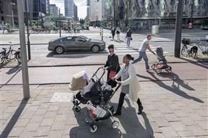 Vriendinnen lopen met hun kinderen in een wandelwagen door het centrum van Rotterdam.