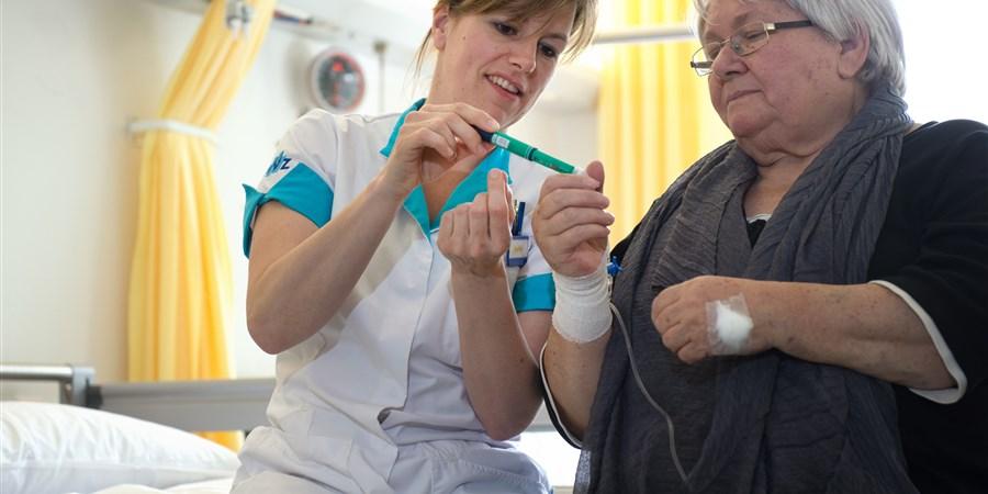 Een verpleegkundige geeft uitleg over het gebruik van een insulinepen aan een van haar patienten.