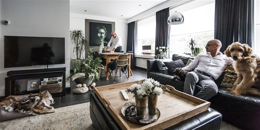 2 mannen en hun hond in een woonkamer