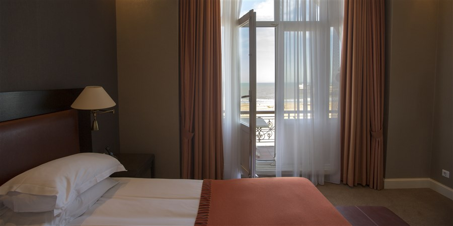 Suite in het Kurhaus aan de zeezijde met uitzicht op de boulevard en het strand.