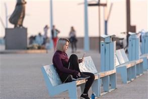 Jonge vrouw zit alleen op een bankje aan een boulevard en kijkt op haar telefoon