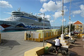 Cruise ship and tourists in harbour Kralendijk with old cannon in Bonaire.