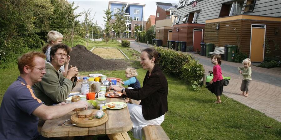 ouders lunchen met hun kinderen in het groen van een ecowijk.