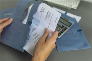 Iemand haalt de belastingaanslag uit de enveloppe