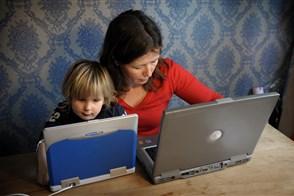 Vrouw met kind aan tafel achter laptop