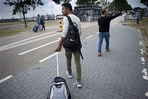 Asielzoekers op het terrein voor het aanmeldcentrum en asielzoekerscentrum