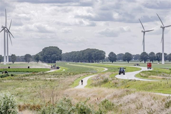 Landschap in Flevoland met windmolens, fietser, vrachtwagen, tractor en boer die mest uitrijdt.