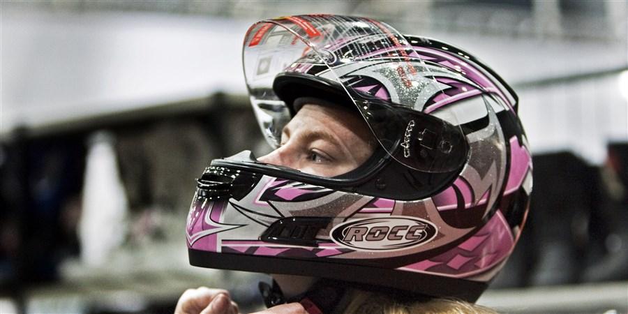 Jonge vrouw past motorhelm op beurs