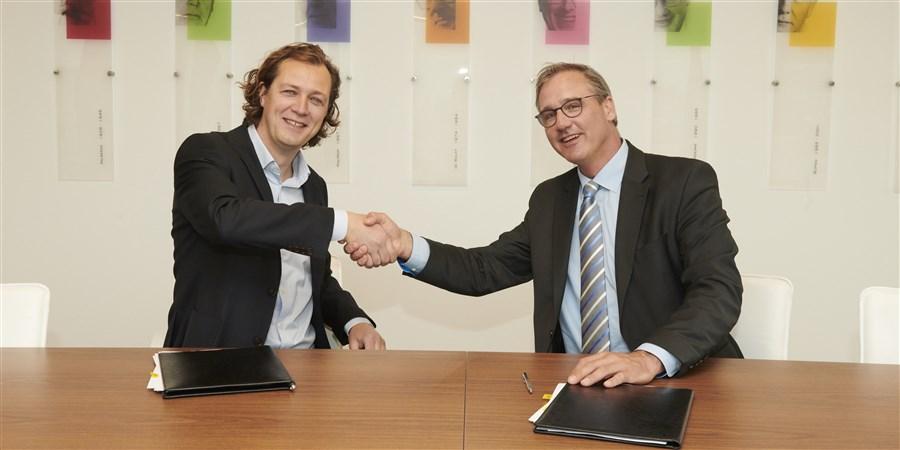 Gijs Barends, medeoprichter van Dataprovider, en plaatsvervangend directeur-generaal Bert Kroese ondertekenen een samenwerkingsovereenkomst.