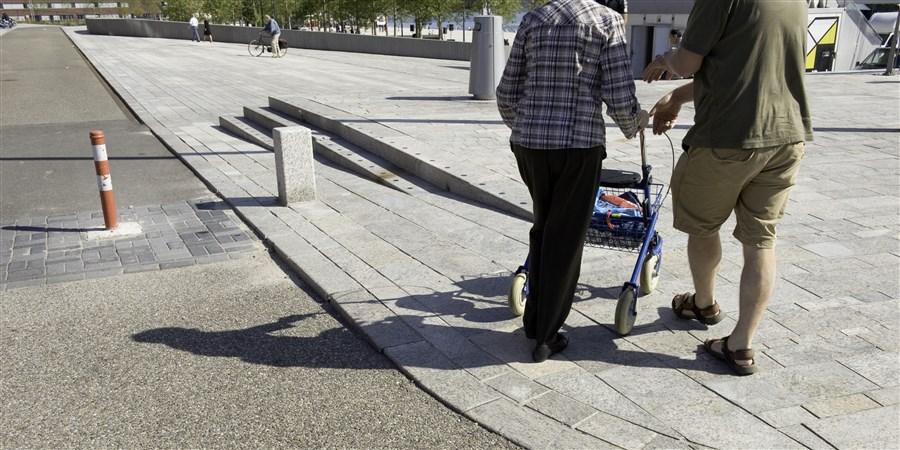 Vrouw met rollator en man lopen op straat