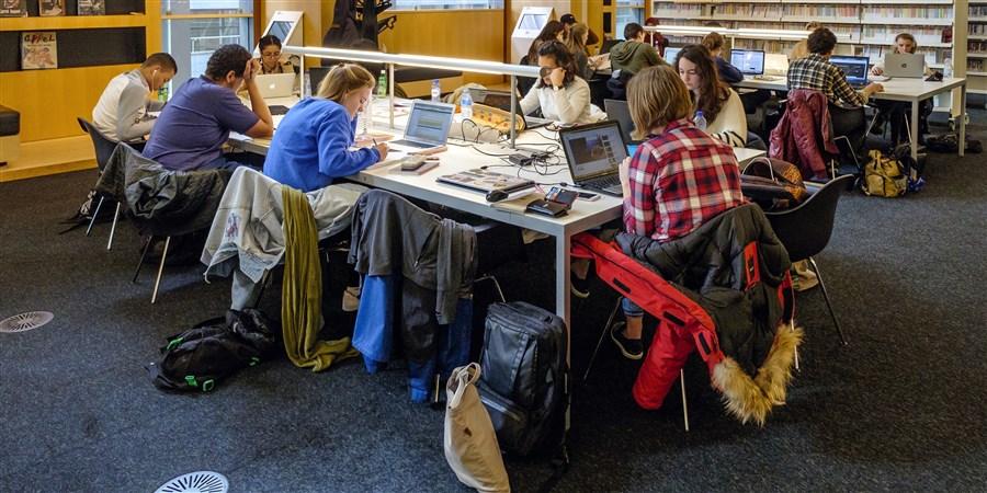 Studenten zitten achter hun laptops aan grote tafel in de bibliotheek.
