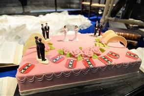 Roze huwelijkstaart met poppetjes erop die het homohuwelijk verbeelden