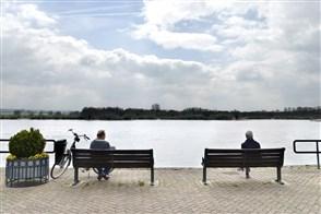 Twee oudere mannen rusten uit op een bankje aan de Waal, Rijn en kijken naar de schepen die voorbijkomen.