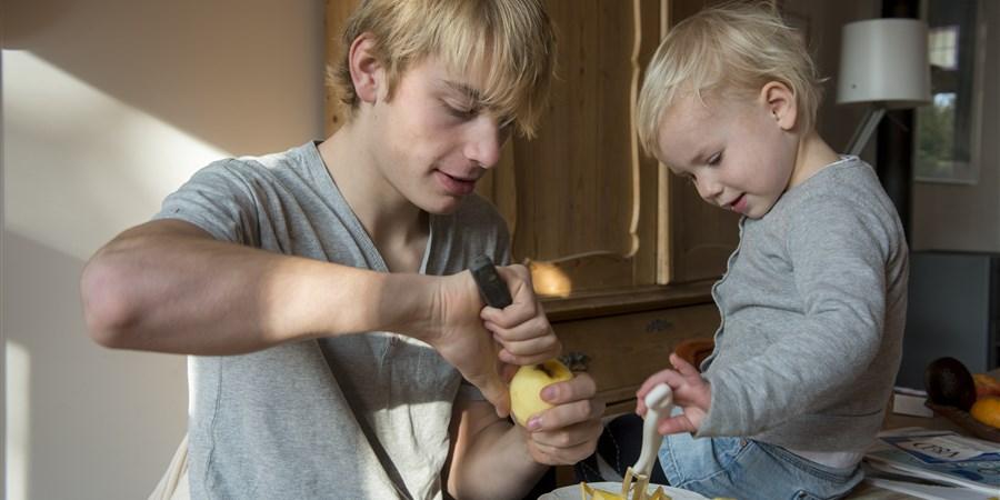 Kind schilt samen met ouder, verzorger een appel