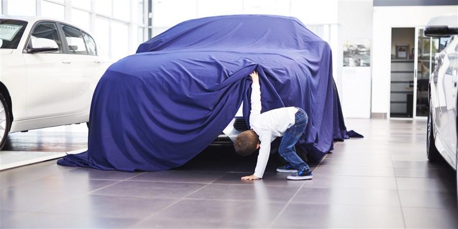 Jongetje kijkt in een autoshowroom stiekem naar een nieuwe auto onder een paars doek