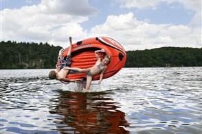 Een jongen en meisje vallen uit rubberbootje dat door hun vader in de lucht wordt omgegooid. Ze zijn op vakantie in Frankrijk en spelen en in het water.
