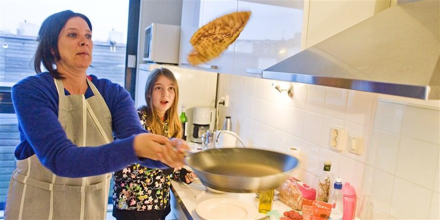 Moeder gooit pannenkoek omhoog, dochter kijkt ernaar