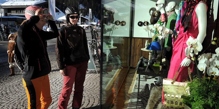 2 wintersportvierders staan voor een etalage in een dorpje in een wintersportgebied
