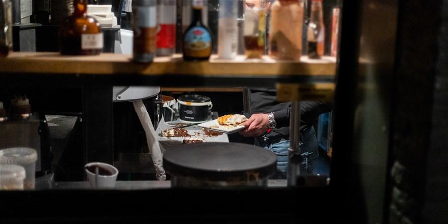 Een man bereidt een wafel in een horecagelegenheid