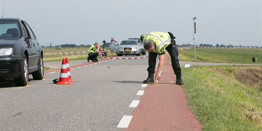 Politieagenten onderzoeken de plek waar een ongeluk is gebeurd