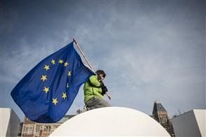 Jongetje plant Europese vlag op een dak.