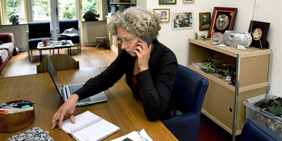 Vrouwelijke ZZP'er zit met laptop en agenda te werken in de woonkamer.