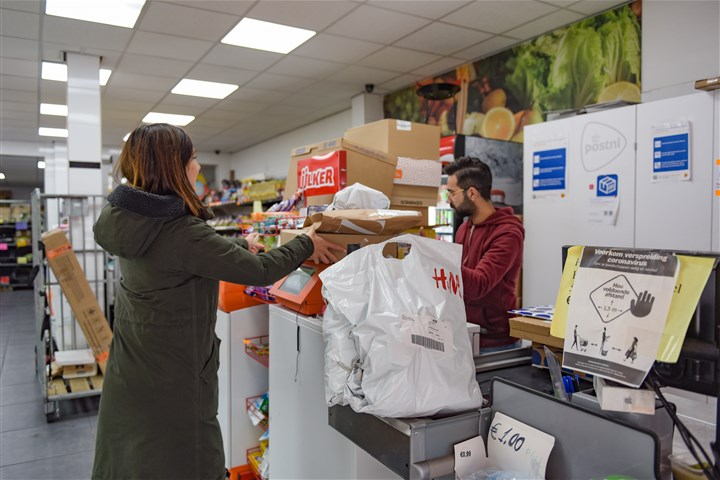 vrouw brengt pakketjes bij postnl punt