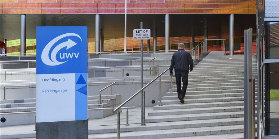 Een man loopt de trap op naar een UWV-kantoor