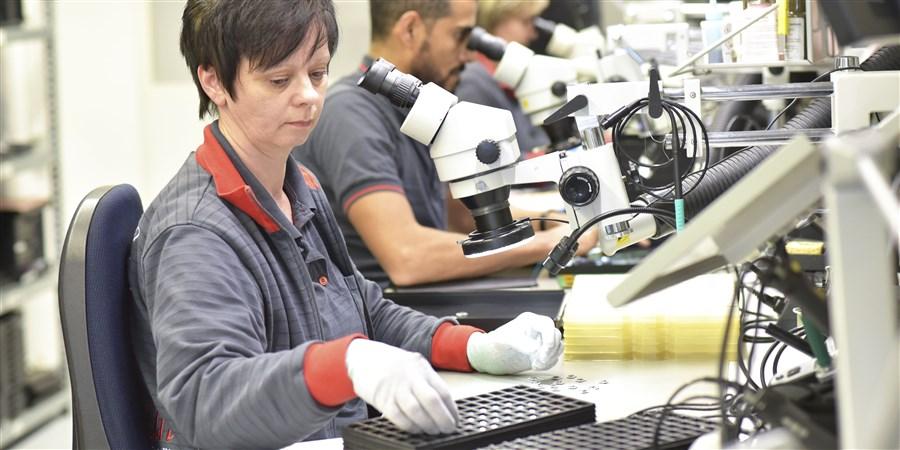 Vrouw aan het werk op de kwaliteitscontrole in de electronische industrie