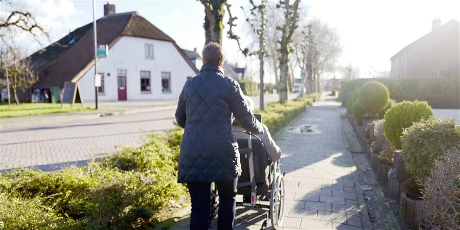 Vrouw wandelt met haar vader die in een rolstoel zit
