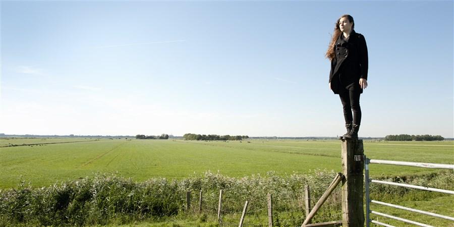 Polder in Baarn,meisje klimt over een hek op een klompenpad in de wei.