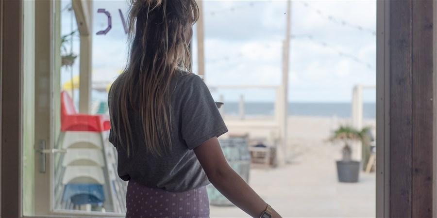 Serveerster kijkt vanuit een strandtent uit over leeg terras