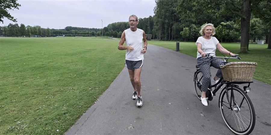 Hardlopende man en fietsende vrouw in groene omgeving